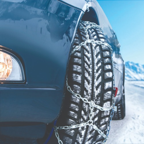 car in snow with tire chains
