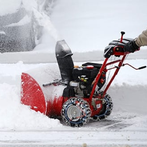 snow blower being pushed while using tire chains